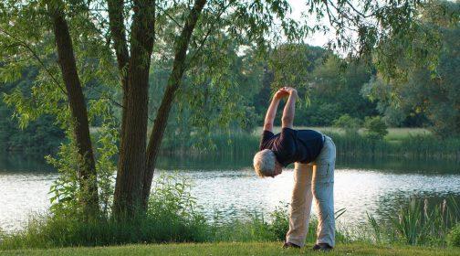 Mann macht Yoga vor einem See